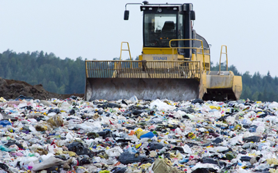 Loader pushing garbage at landfill